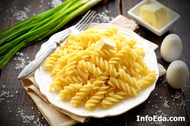 Сваренные макароны с маслом в тарелке